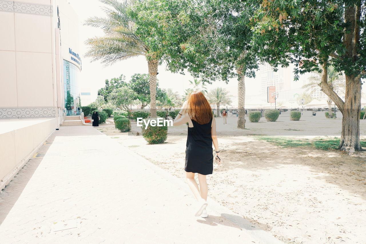 Rear view of woman walking on road in city