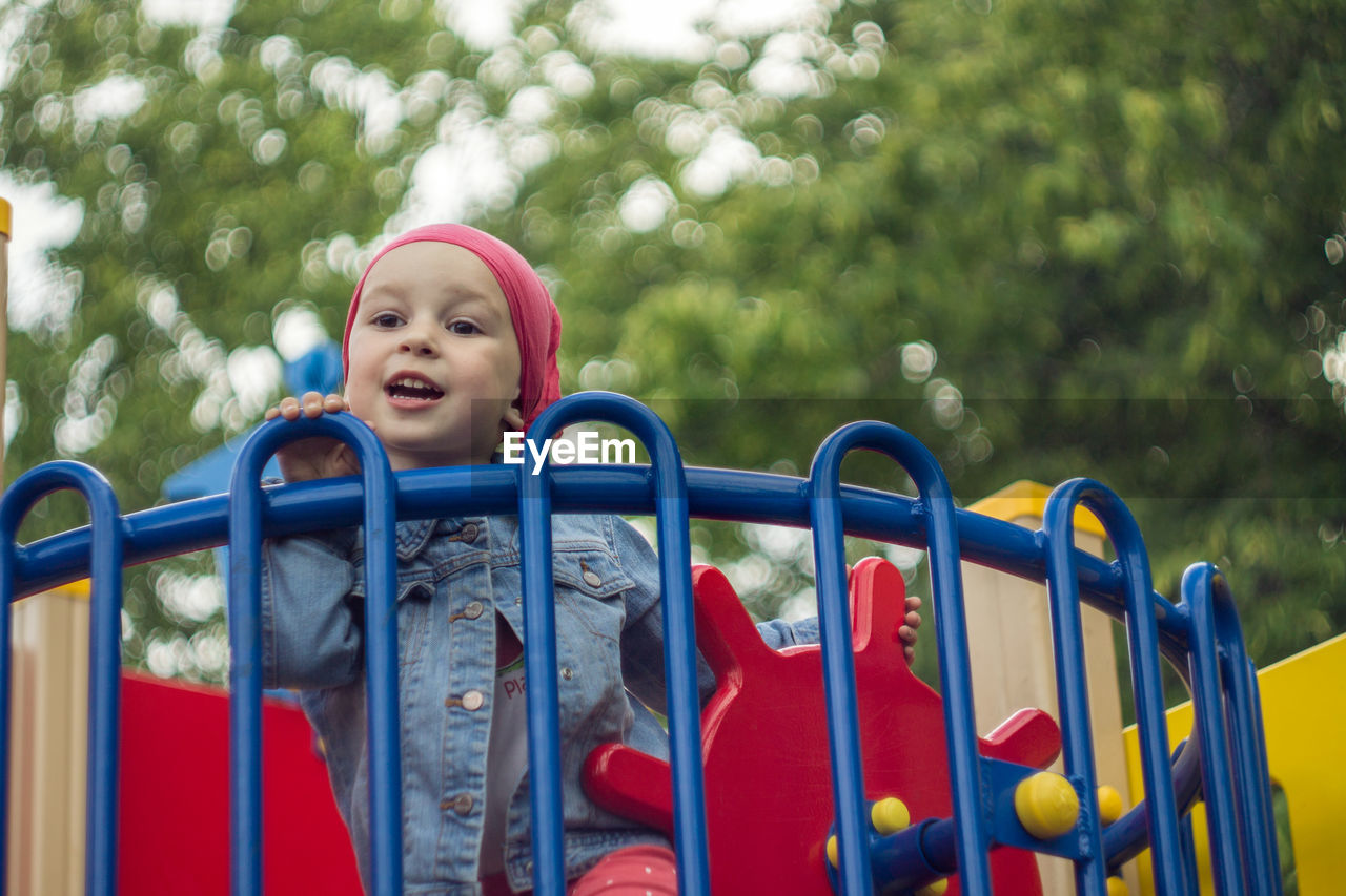 Cute Boy Standing In Outdoor Play Equipment At Park