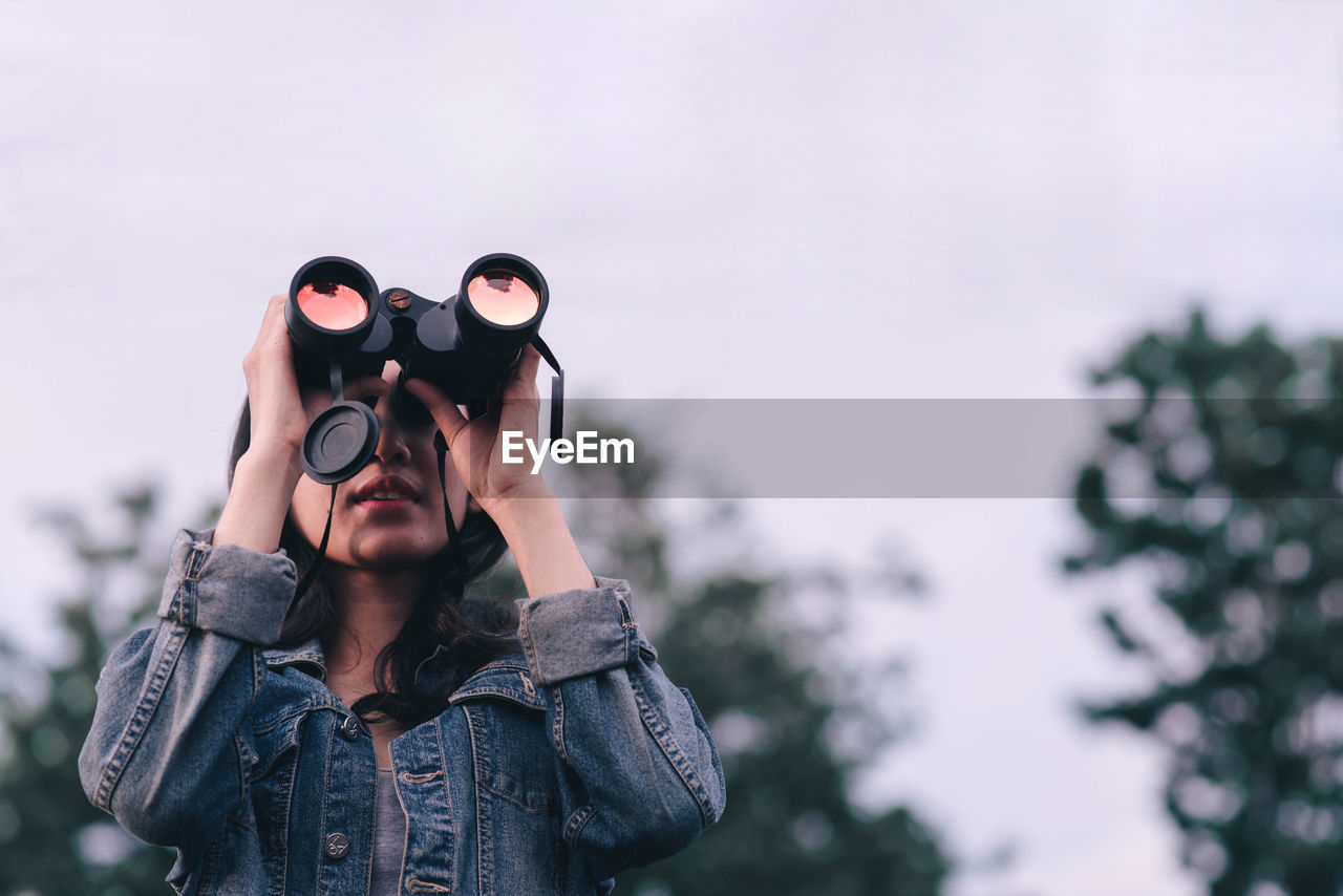 Young Woman Looking Through Binoculars While Standing Against Sky