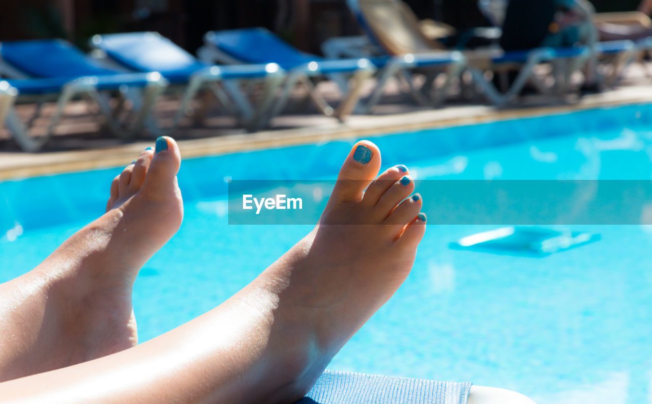 Low section of woman relaxing at swimming pool