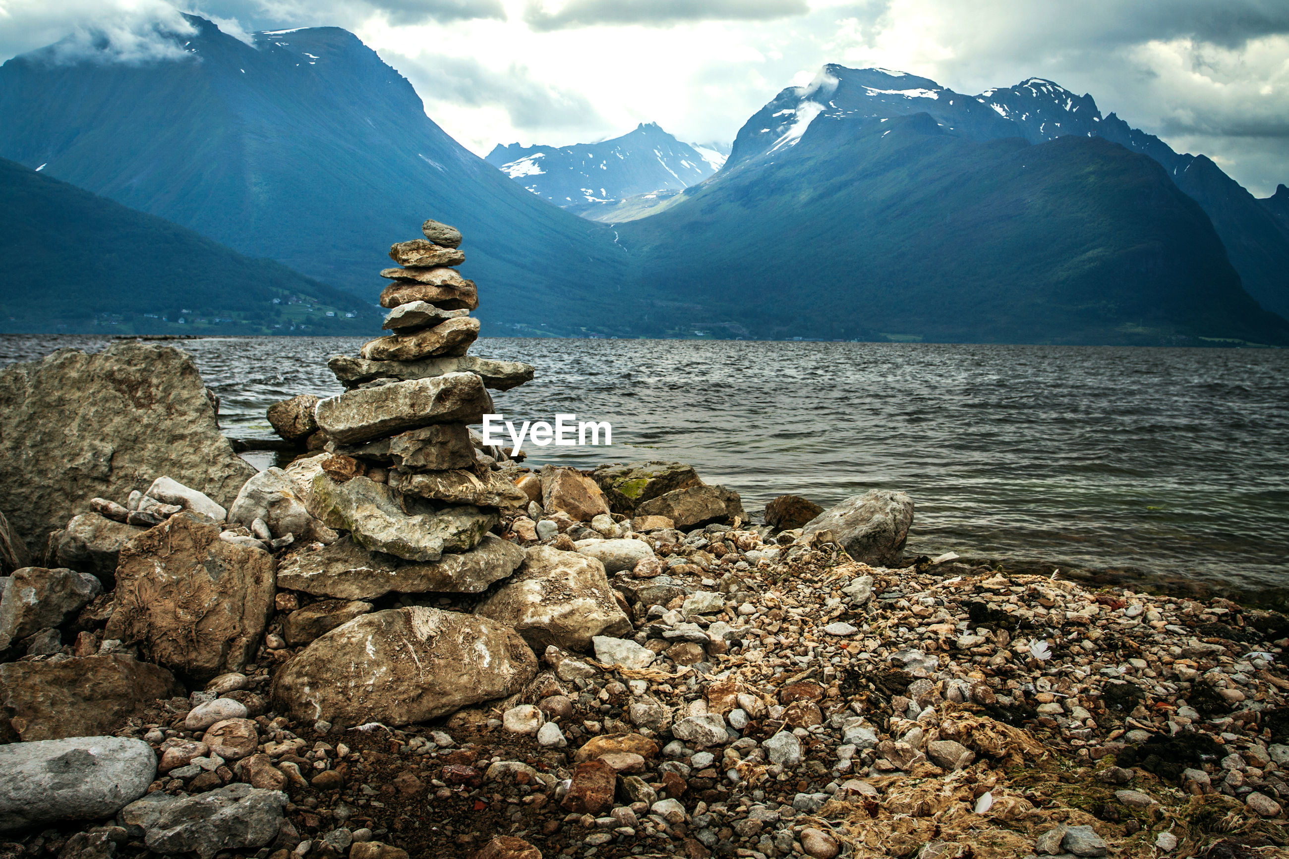 STACK OF ROCKS ON SHORE AGAINST MOUNTAIN