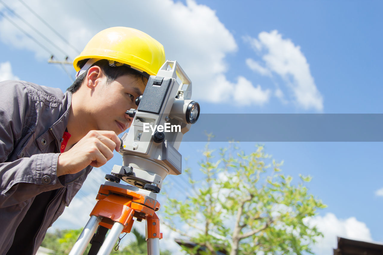 Side view of engineer looking through theodolite at construction site