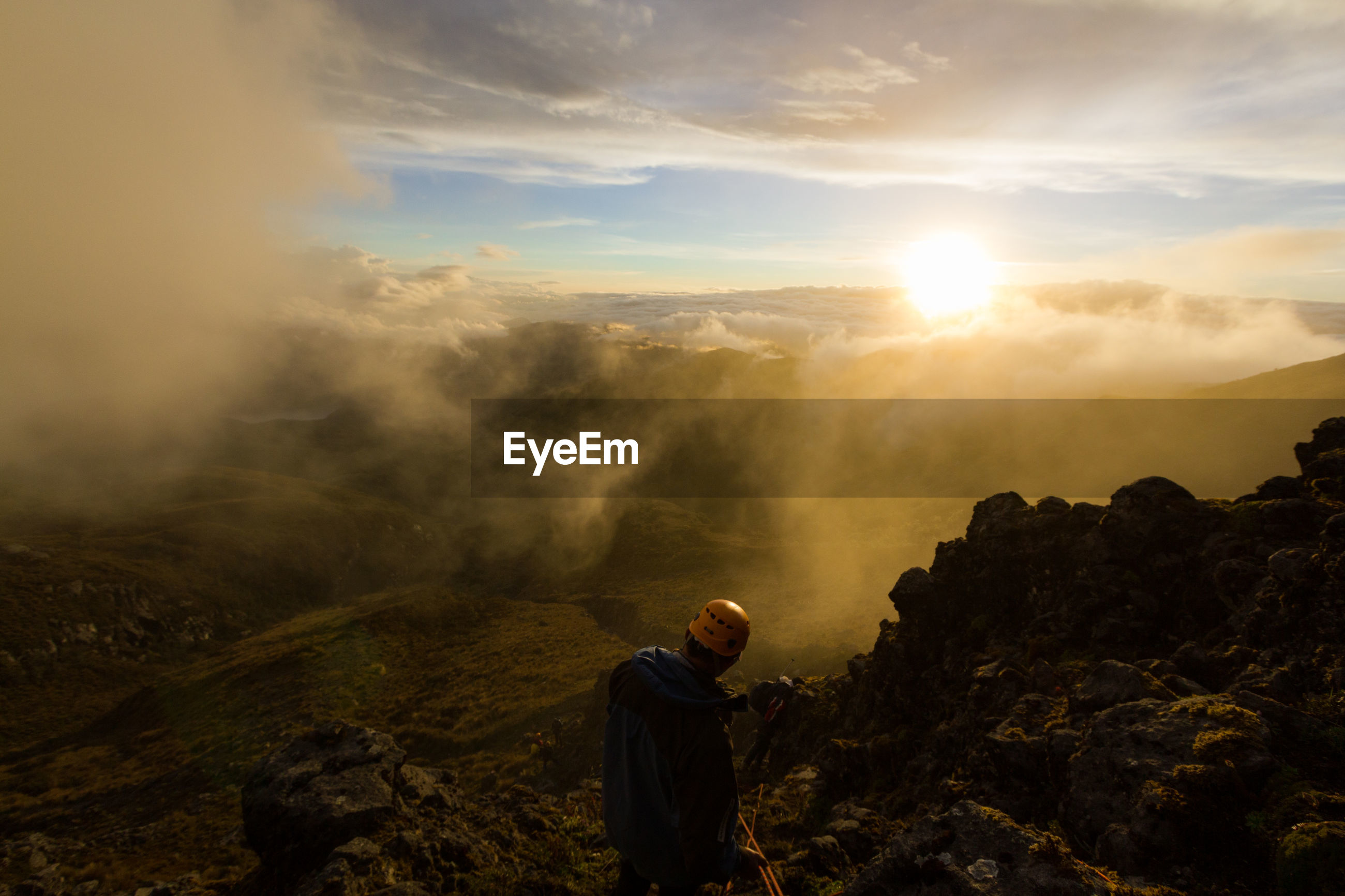 Man walking on mountain against sky during sunset