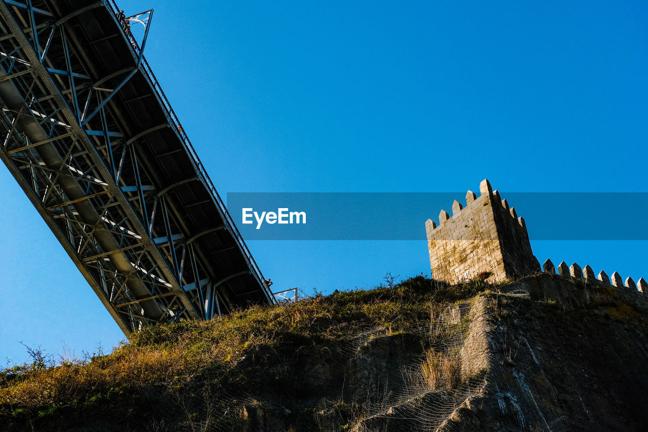 sky, built structure, architecture, low angle view, clear sky, blue, nature, day, no people, connection, copy space, bridge, outdoors, history, sunlight, bridge - man made structure, the past, travel, travel destinations, transportation, ruined