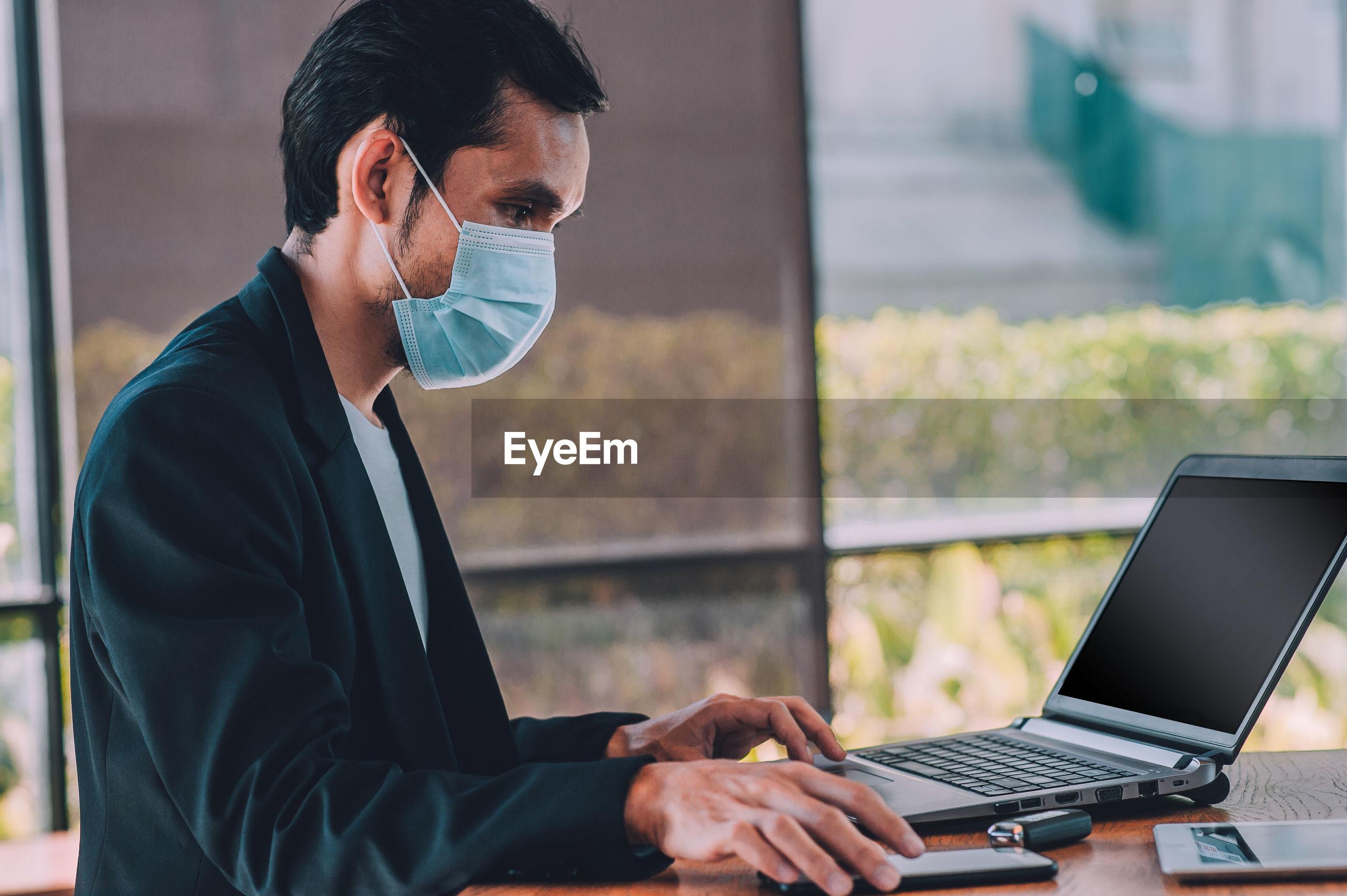 Man wearing mask using laptop at table