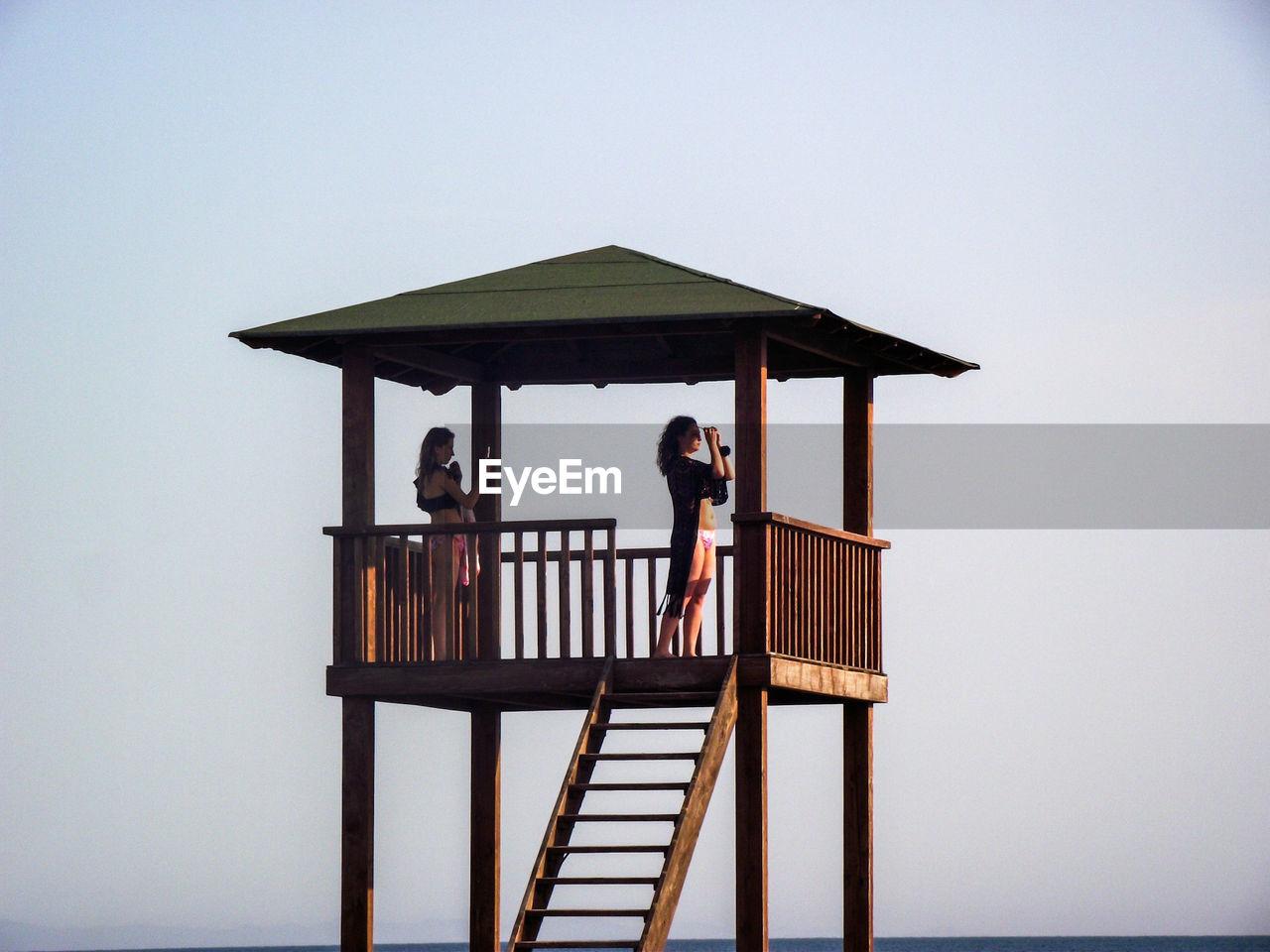 Women standing in lifeguard hut against sky