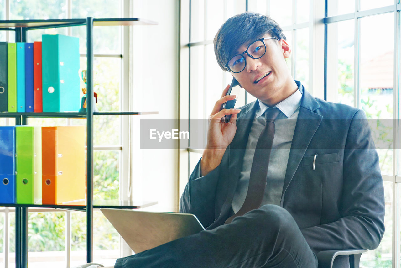 sitting, one person, real people, window, front view, three quarter length, young men, glasses, well-dressed, eyeglasses, men, indoors, young adult, holding, technology, using phone, smiling, communication, wireless technology