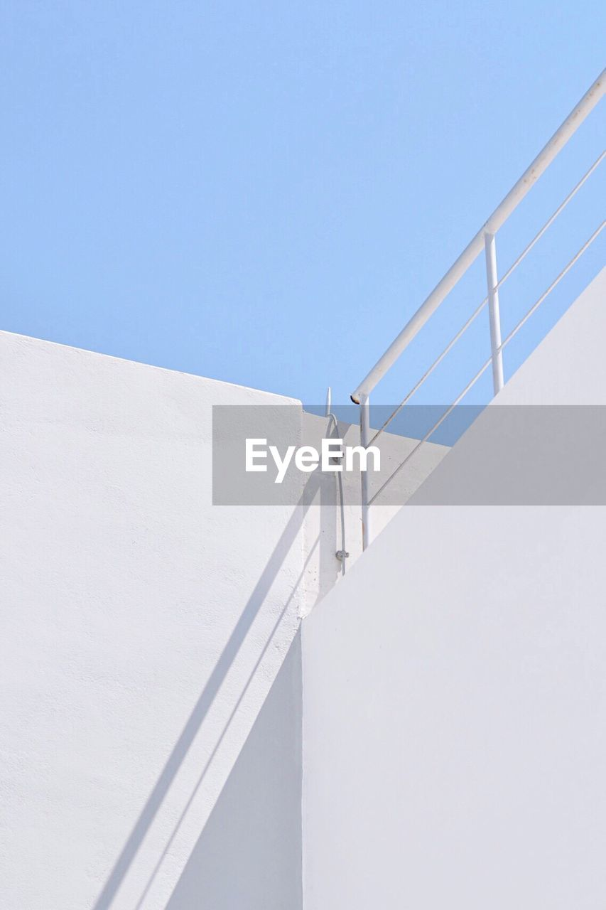 copy space, clear sky, sky, staircase, architecture, white color, railing, day, no people, low angle view, nature, blue, built structure, steps and staircases, sunlight, wall - building feature, outdoors, building exterior, white, shadow