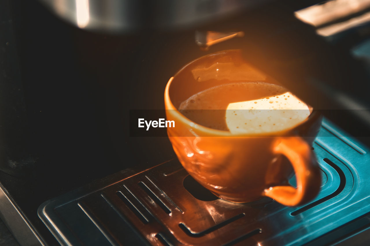 food and drink, drink, refreshment, coffee, freshness, indoors, cup, coffee - drink, still life, close-up, appliance, no people, high angle view, orange color, food, coffee cup, kitchen utensil, household equipment, mug, hot drink, crockery, non-alcoholic beverage, froth