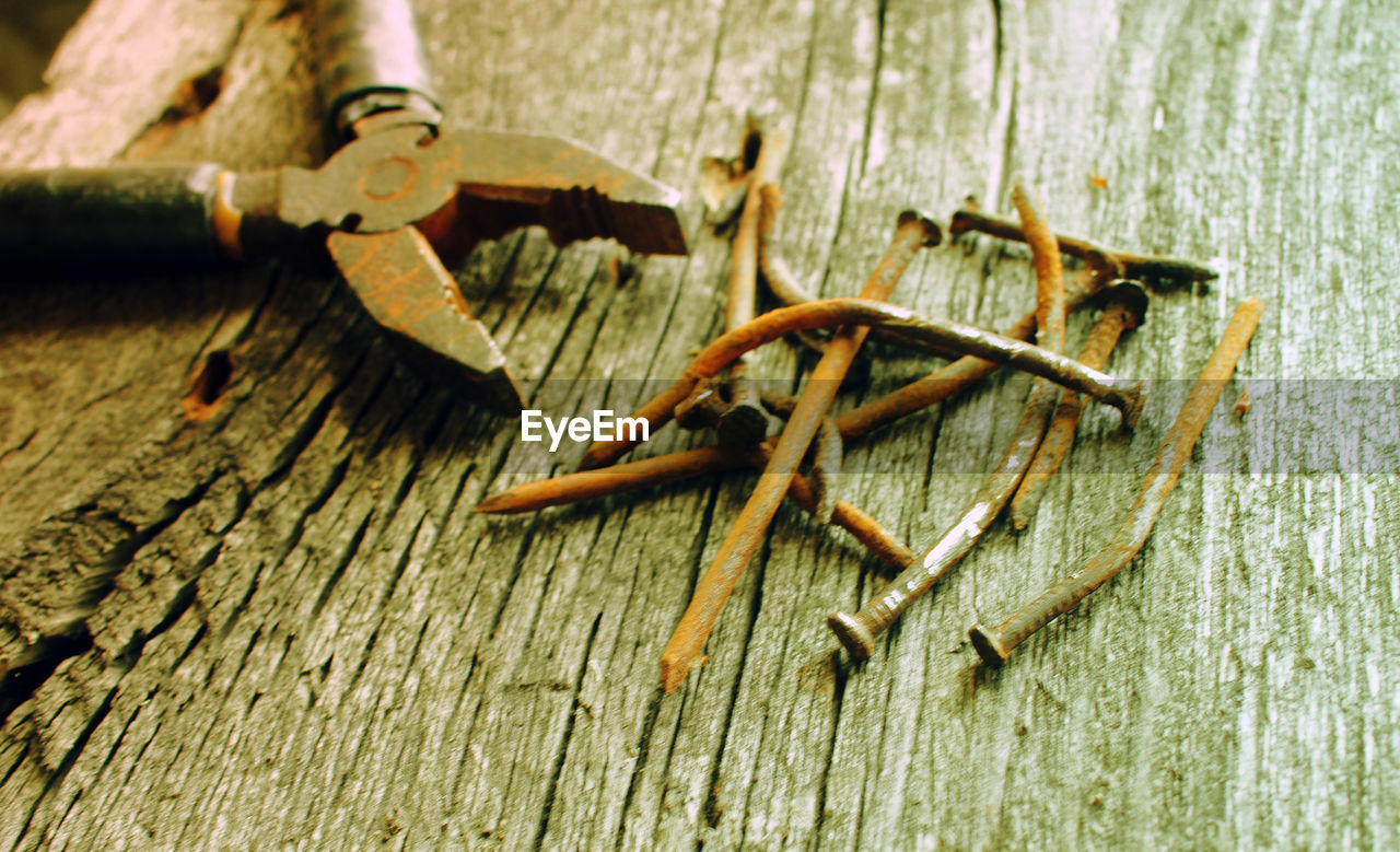 Close-up of old rusty pliers and nails on wooden table