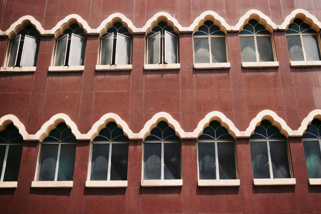 architecture, building exterior, built structure, window, arch, no people, low angle view, day, repetition, in a row, side by side, building, full frame, outdoors, wall, pattern, brick, reflection, backgrounds, brick wall, arched