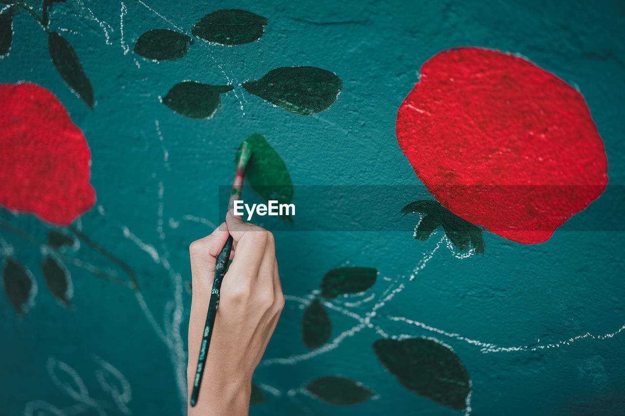Cropped Hand Painting From Flowers On Wall
