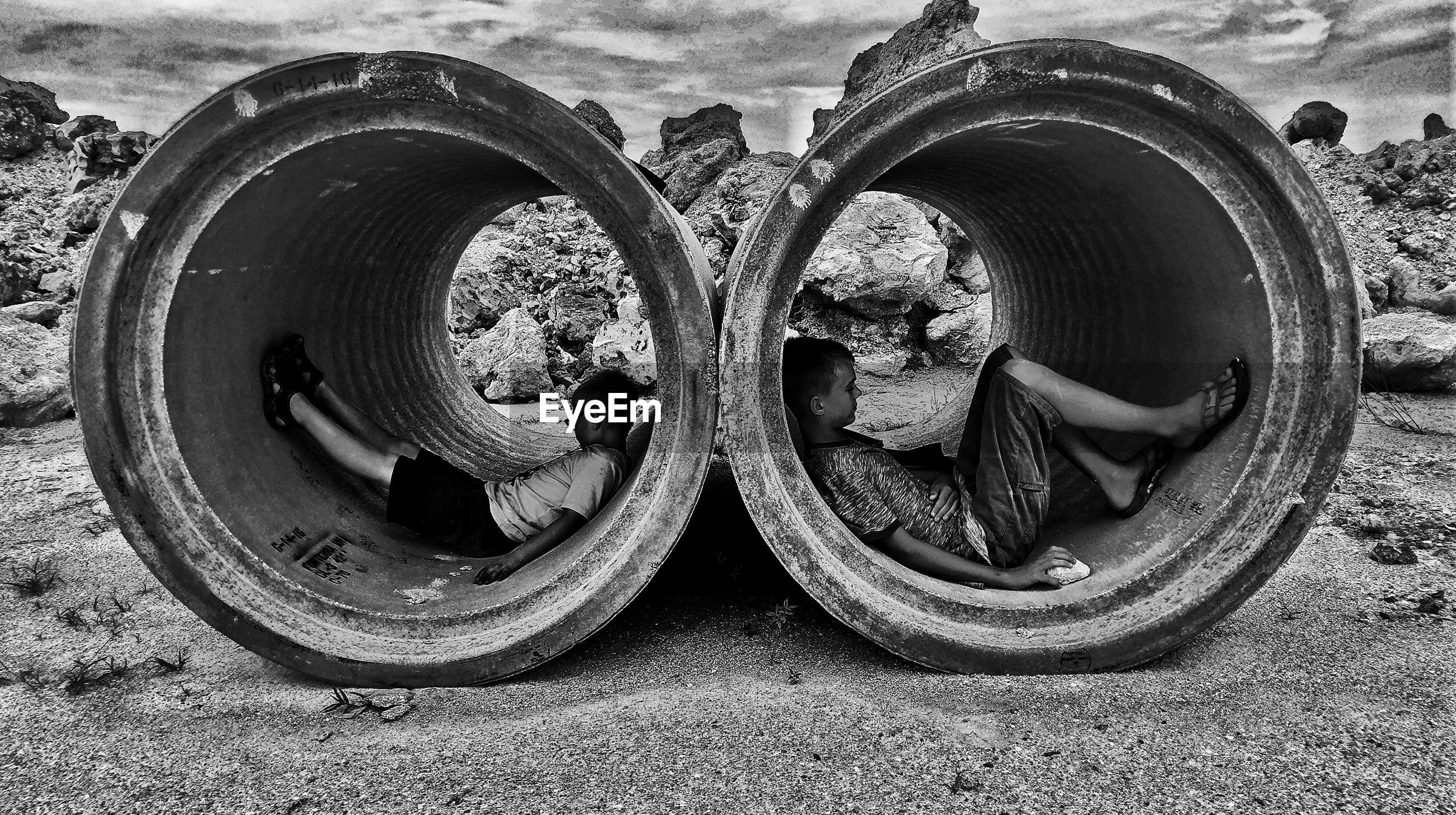 Side view of boys sitting in concrete pipe