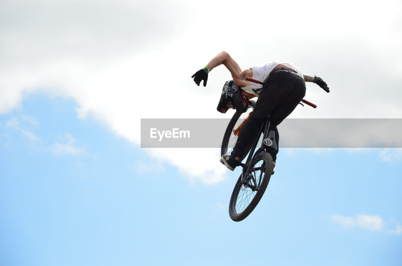 low angle view, sky, real people, men, mid-air, extreme sports, skill, bicycle, cloud - sky, sport, outdoors, day, leisure activity, riding, stunt, jumping, full length, competitive sport, adventure, one person, competition, nature, people