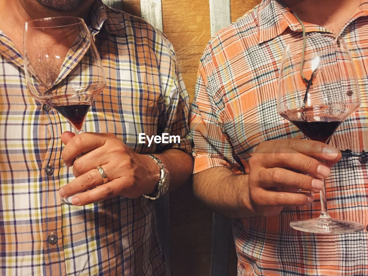 Close-Up Of Hands Holding Wine Glasses