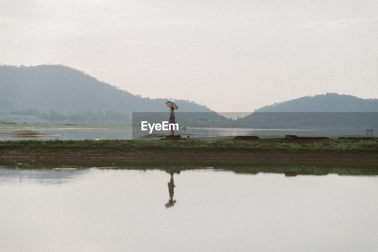 Full length of young woman standing by water against sky