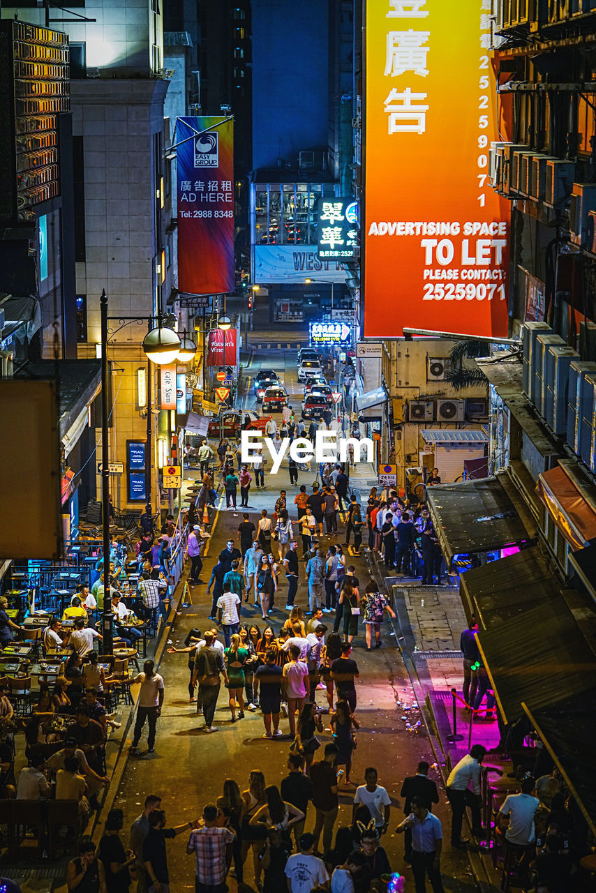 group of people, city, crowd, large group of people, architecture, real people, building exterior, built structure, street, illuminated, transportation, city life, text, men, night, city street, lifestyles, high angle view, walking, outdoors, consumerism