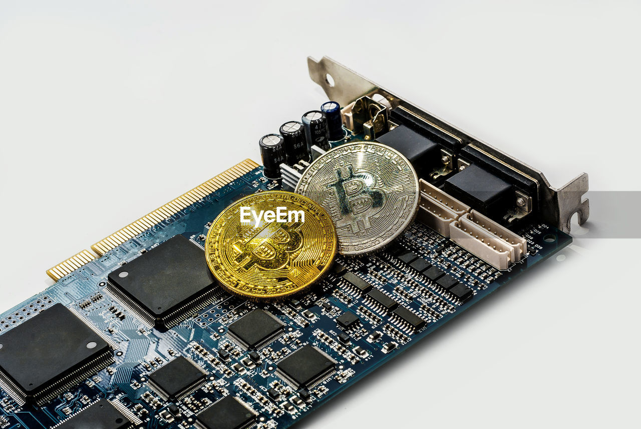 Close-up of bitcoins on computer equipment against white background