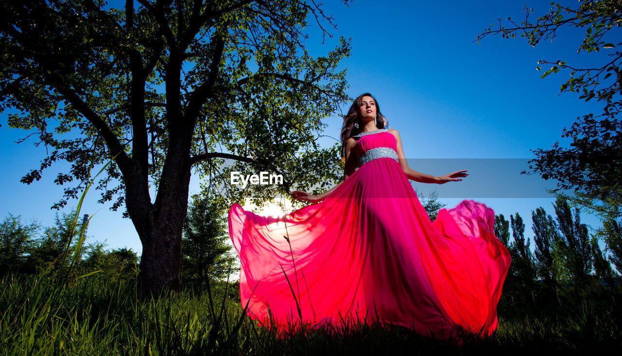 plant, tree, one person, young adult, real people, women, dress, young women, nature, lifestyles, grass, leisure activity, fashion, field, low angle view, sky, land, pink color, clothing, outdoors, beautiful woman, hairstyle