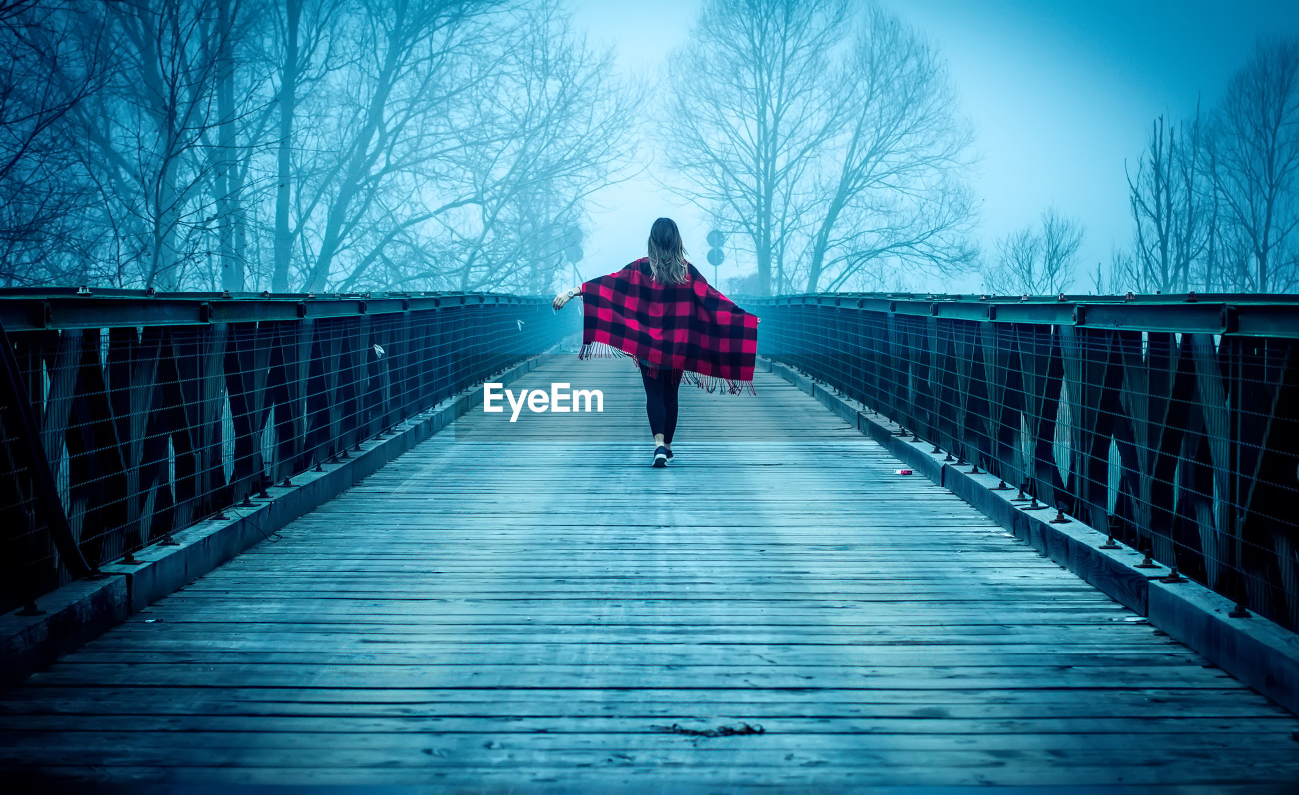 Rear view of woman walking on bridge against sky during foggy weather
