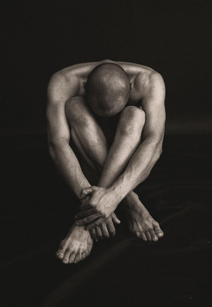 Full Length Of Naked Male Model Sitting Against Black Background