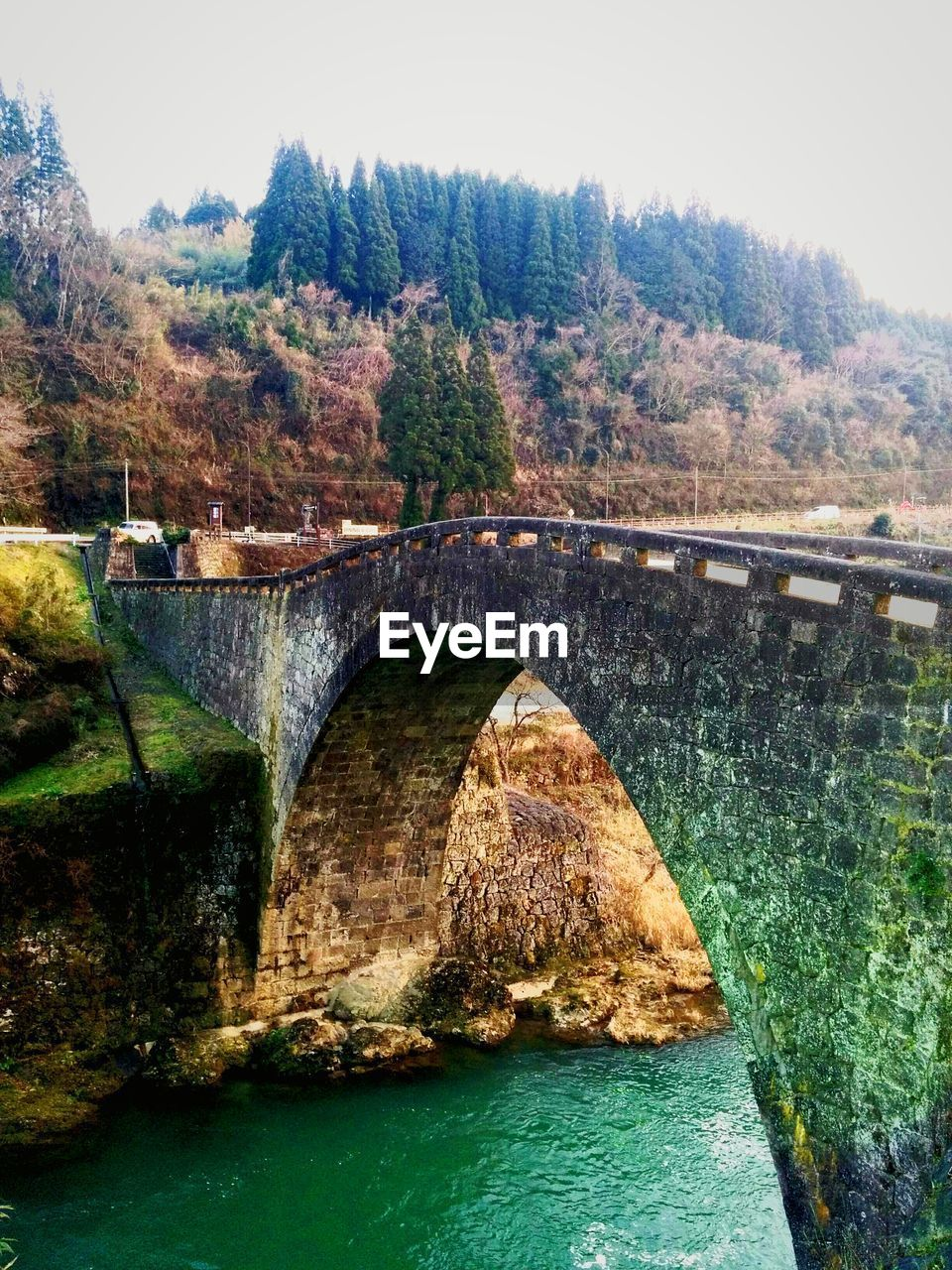 bridge - man made structure, connection, arch bridge, river, architecture, engineering, water, built structure, tree, arch, bridge, nature, outdoors, day, transportation, no people, dam, tranquility, scenics, beauty in nature, sky