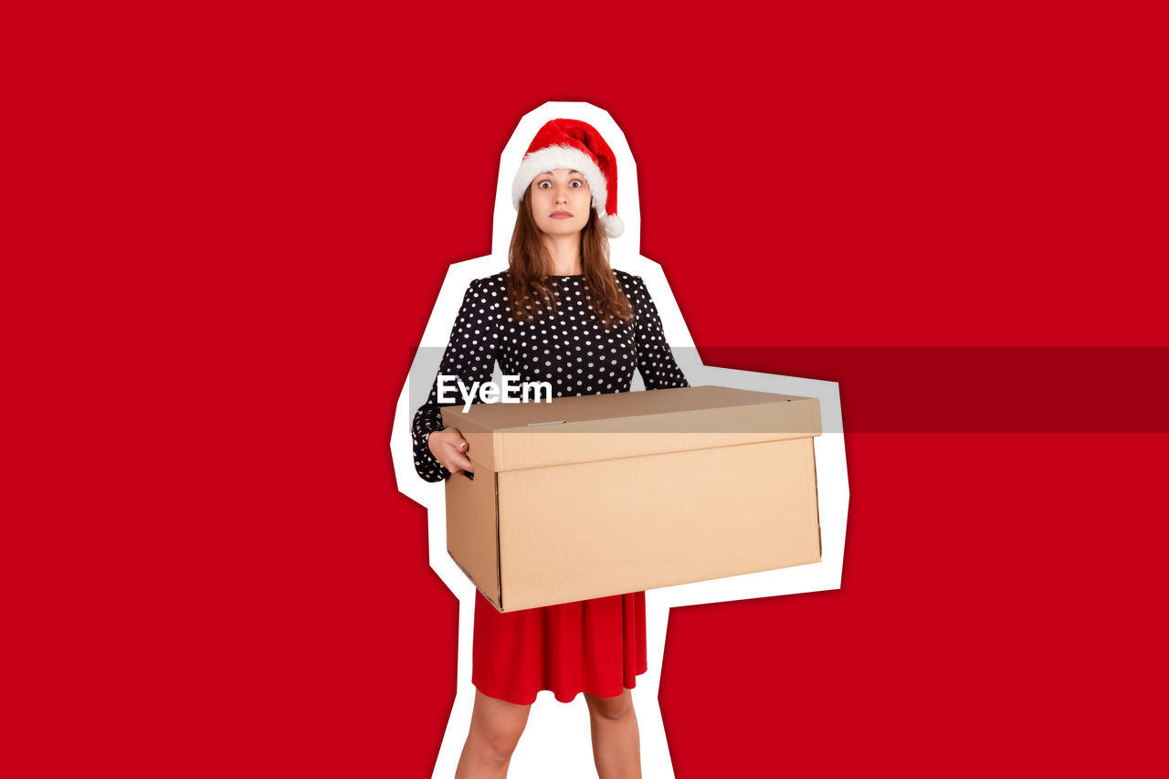 Portrait of shocked woman holding box against red background