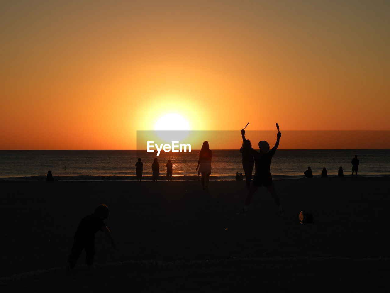 sunset, sun, silhouette, beach, nature, orange color, beauty in nature, sea, real people, leisure activity, scenics, lifestyles, water, horizon over water, vacations, beach volleyball, enjoyment, fun, playing, net - sports equipment, volleyball - sport, sunlight, weekend activities, sky, outdoors, men, large group of people, togetherness, people