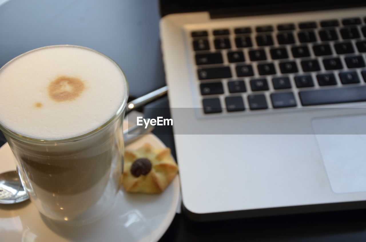 High Angle View Of Coffee Cup By Laptop On Table