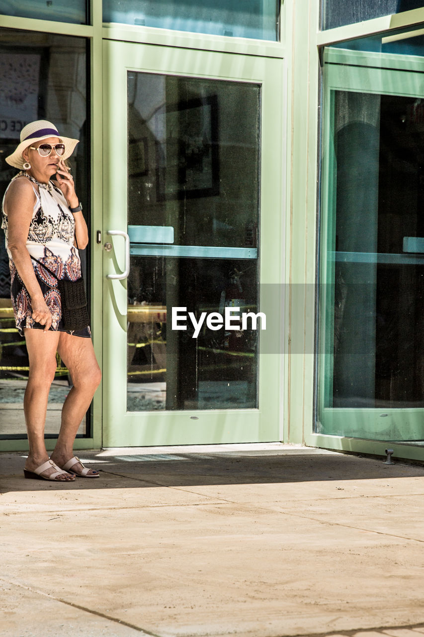 glass - material, building exterior, architecture, window, reflection, built structure, real people, standing, one person, day, transparent, women, full length, lifestyles, leisure activity, adult, casual clothing, building, outdoors