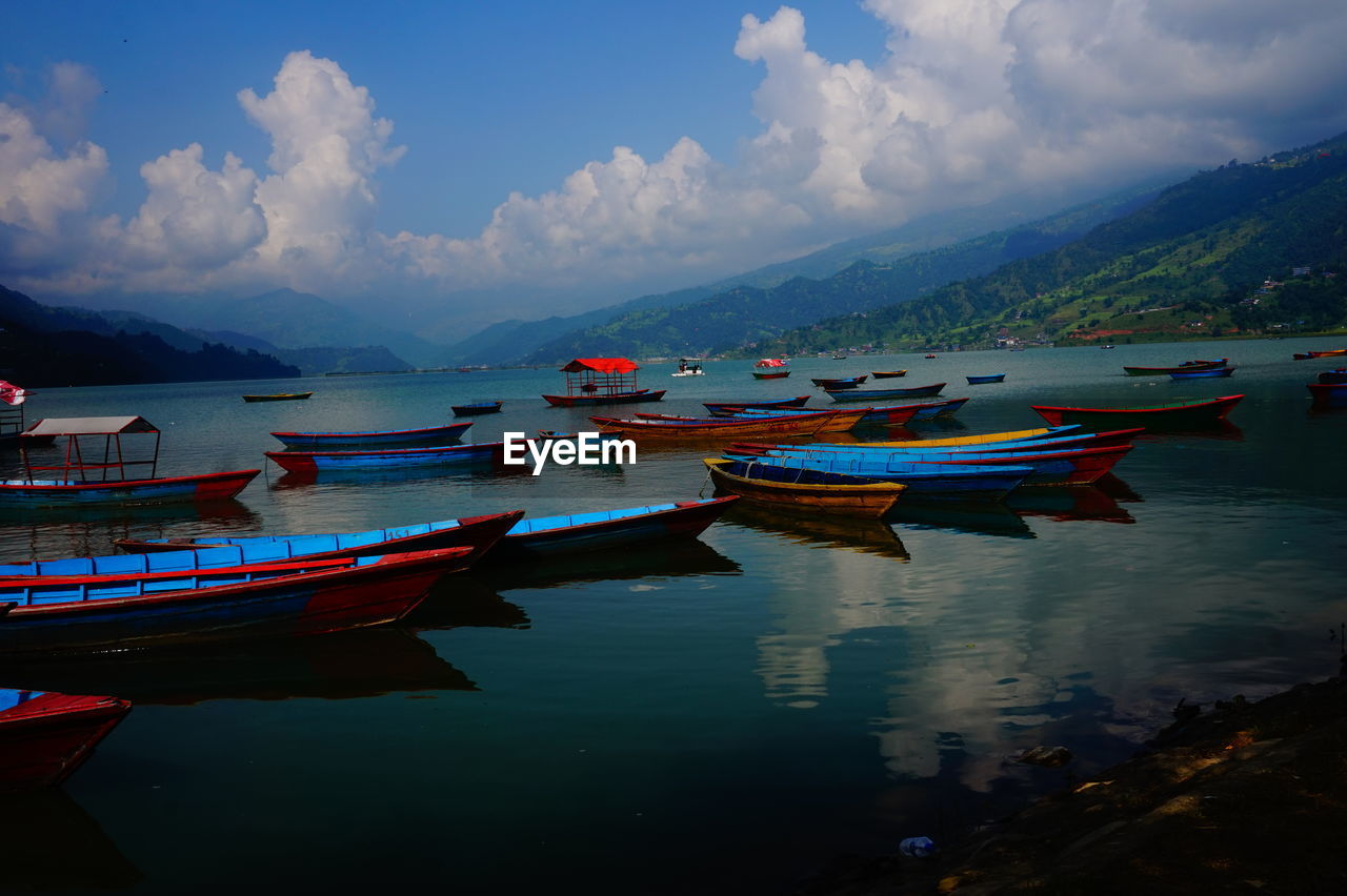 BOATS MOORED ON SEA BY MOUNTAINS AGAINST SKY
