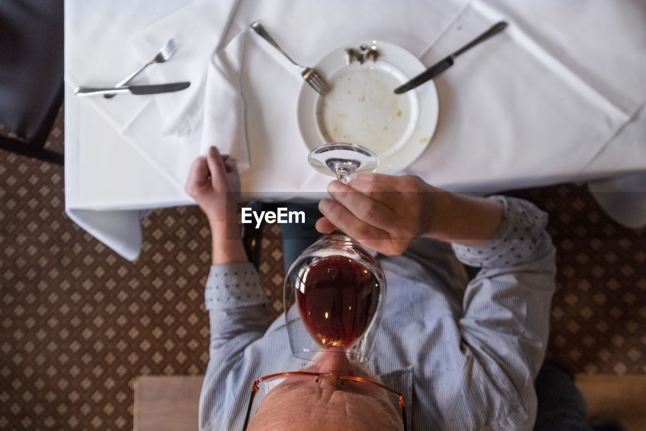 Directly above view of man drinking wine at restaurant