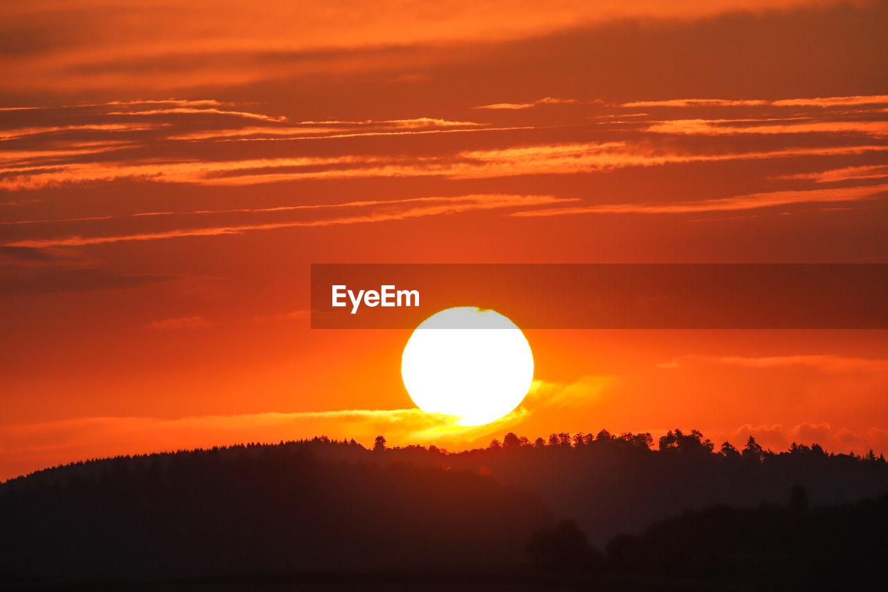 sunset, beauty in nature, sky, orange color, scenics - nature, cloud - sky, sun, tranquil scene, tranquility, silhouette, idyllic, non-urban scene, nature, circle, sunlight, geometric shape, no people, tree, shape, environment, outdoors, eclipse, romantic sky, brightly lit