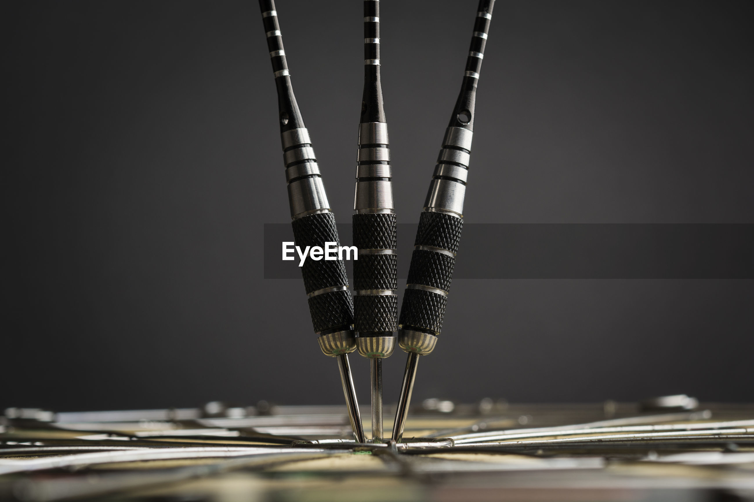 Close-up of darts on board against black background