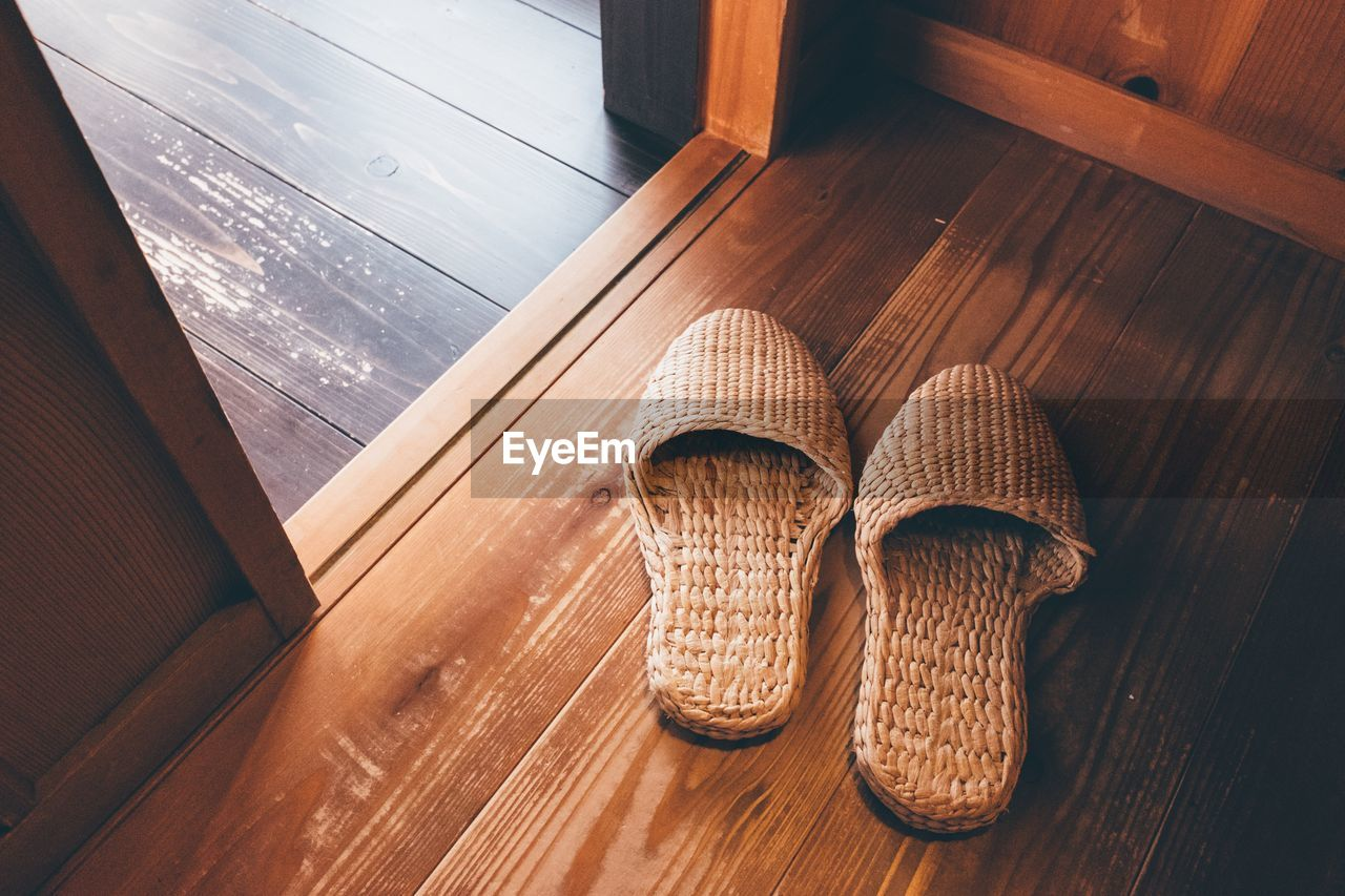 High Angle View Of Wicker Slippers On Floorboard