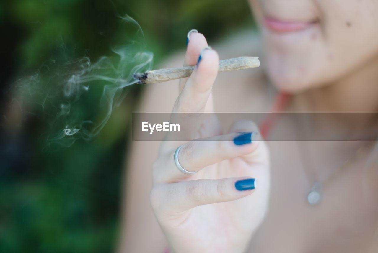 Midsection Of Woman Smoking Marijuana Joint