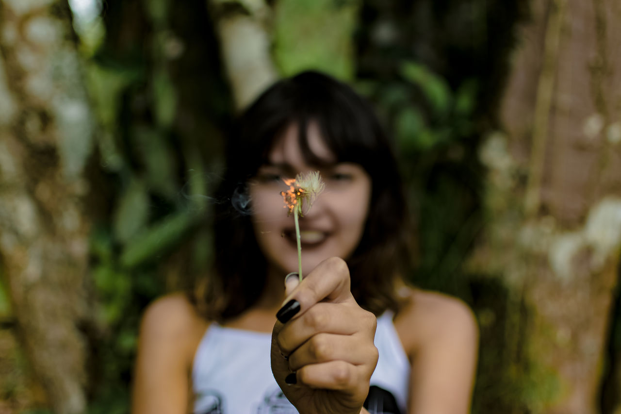 Young Woman Holding Burning Dandelion Against Trees