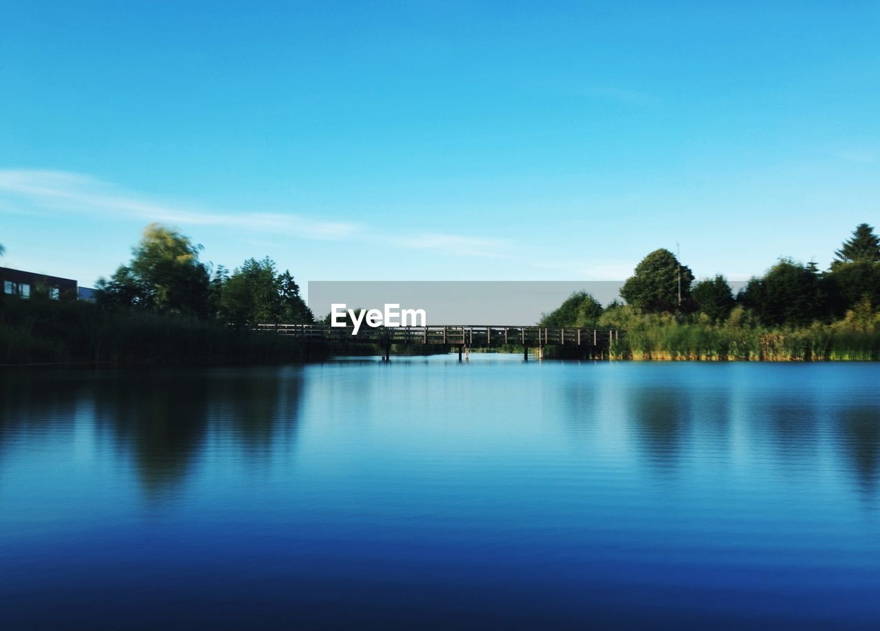 View of calm lake against blue sky