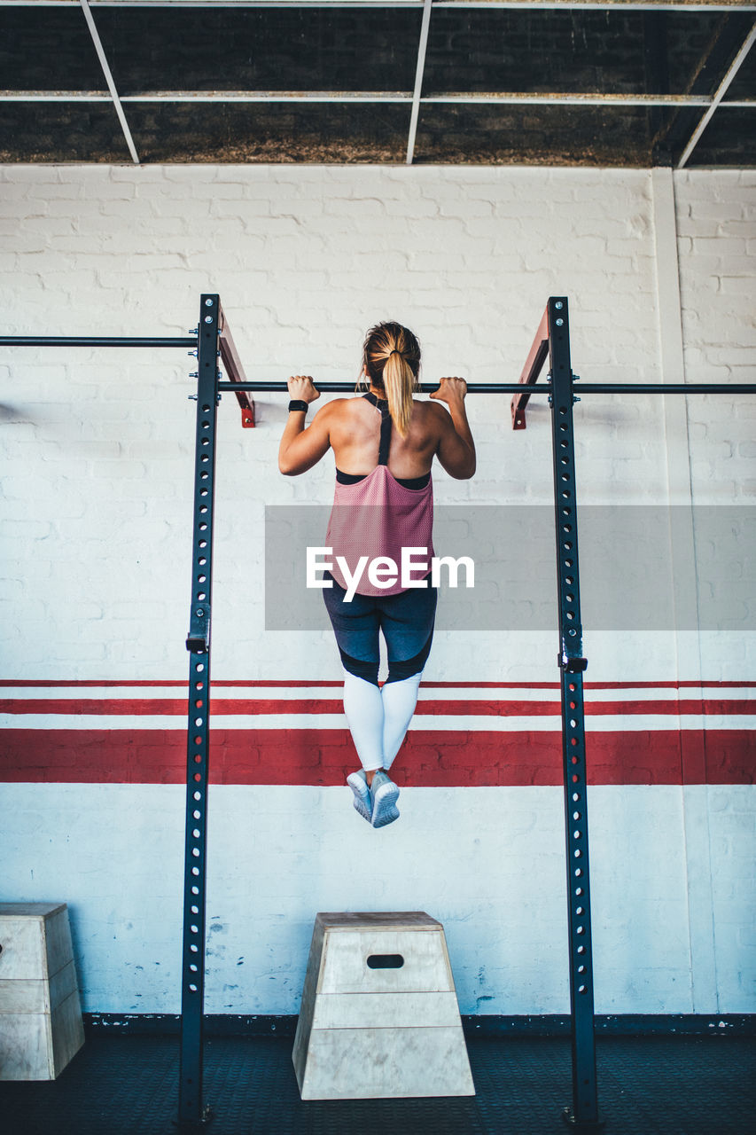 Full Length Rear View Of Woman Exercising In Gym