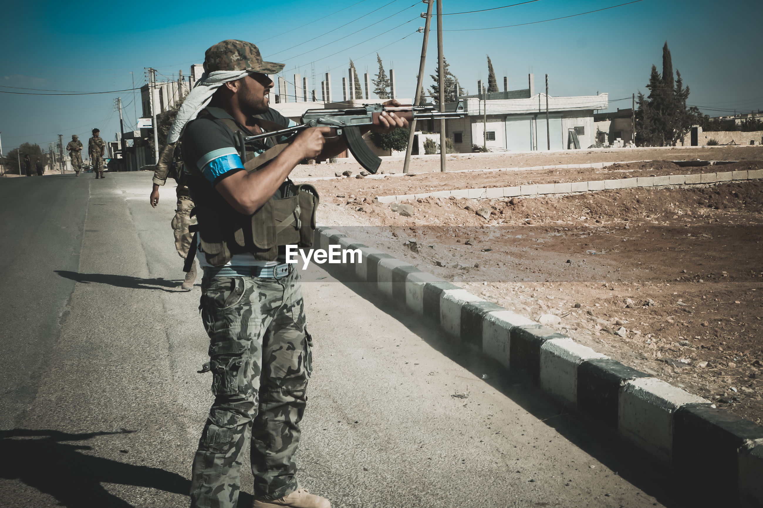 Terrorist holding rifle while standing on road