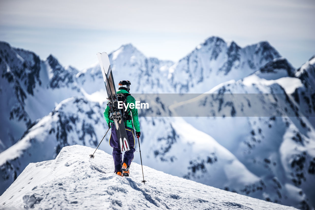 Man hiking on snowcapped mountain peak while looking at landscape against sky