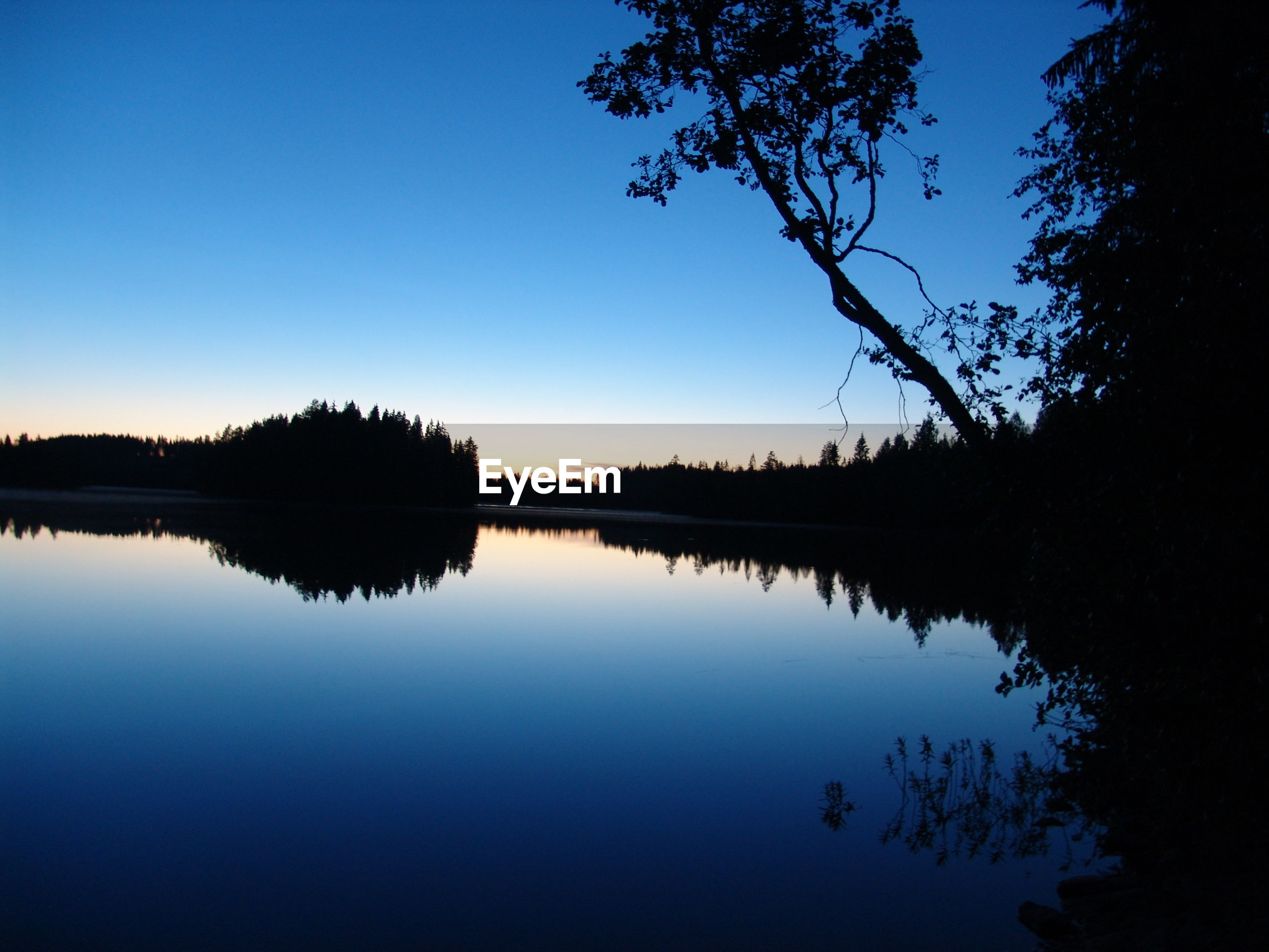 SCENIC VIEW OF CALM LAKE AGAINST CLEAR SKY AT DUSK