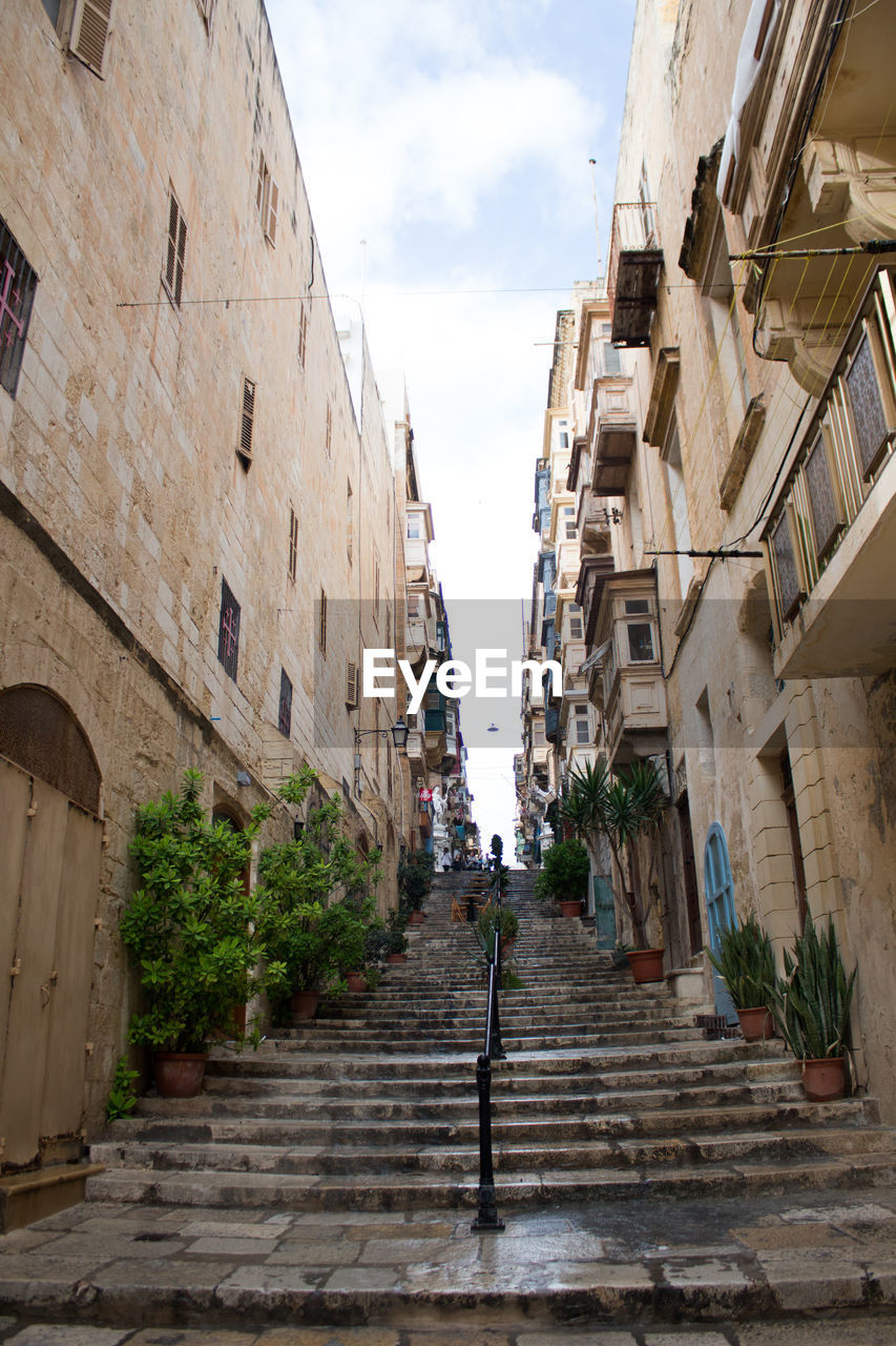 architecture, built structure, building exterior, staircase, city, sky, building, the way forward, cloud - sky, direction, residential district, nature, steps and staircases, day, low angle view, street, incidental people, plant, town, outdoors, alley