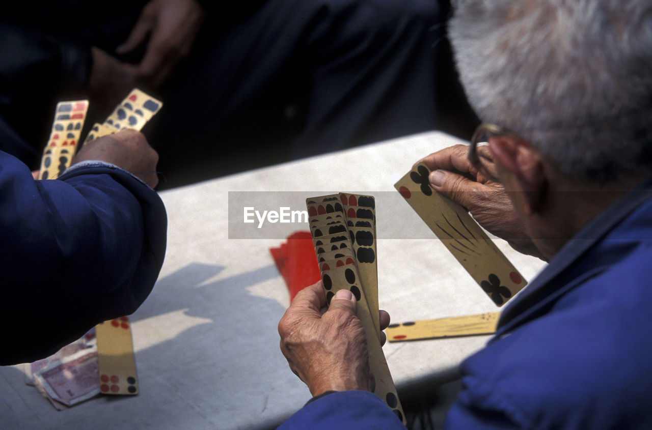 Cropped Image Of Senior Men Playing Cards On Table