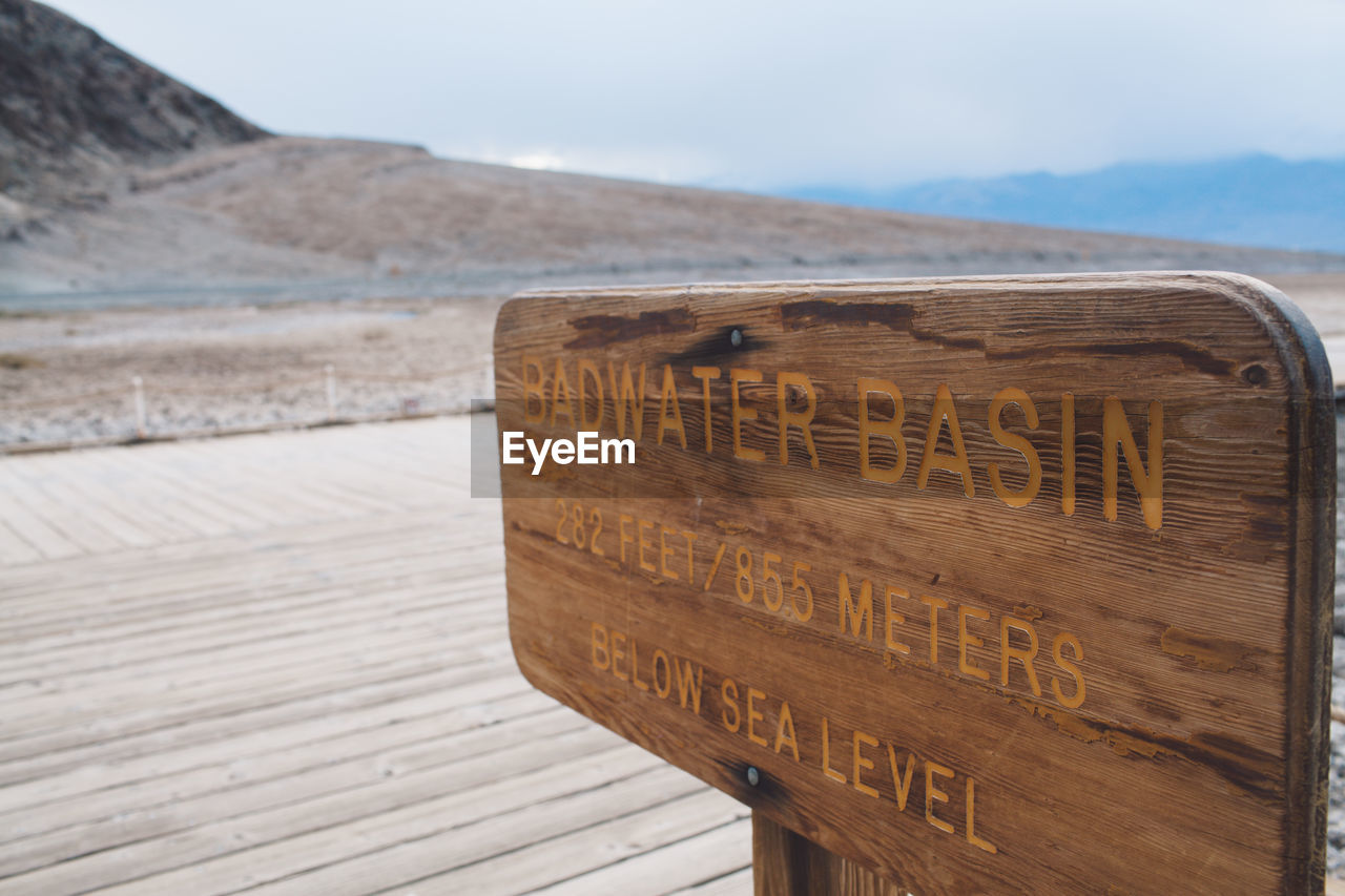Close-Up Of Text On Wood At Beach Against Sky