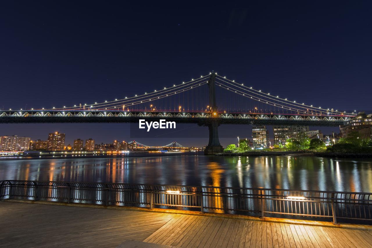 Illuminated manhattan bridge over east river against sky seen from pier