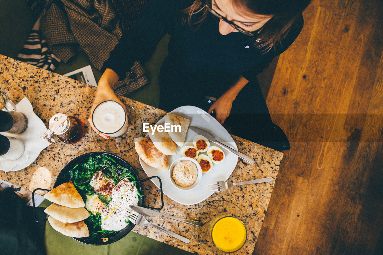 table, high angle view, food, food and drink, real people, plate, breakfast, coffee - drink, bread, indoors, healthy eating, one person, ready-to-eat, freshness, lifestyles, human hand, day, close-up