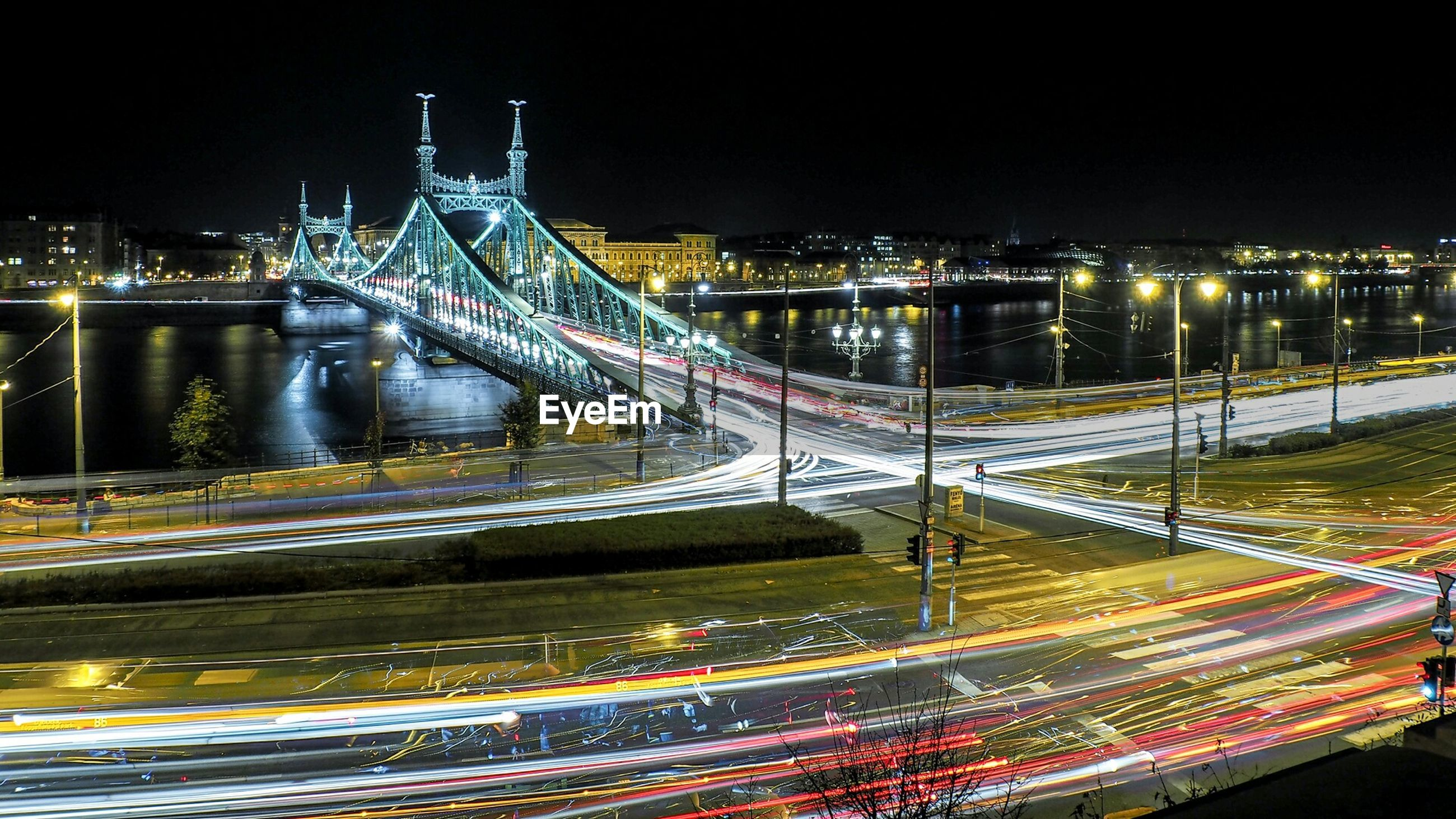 High angle view of light trails on road and bridge at night
