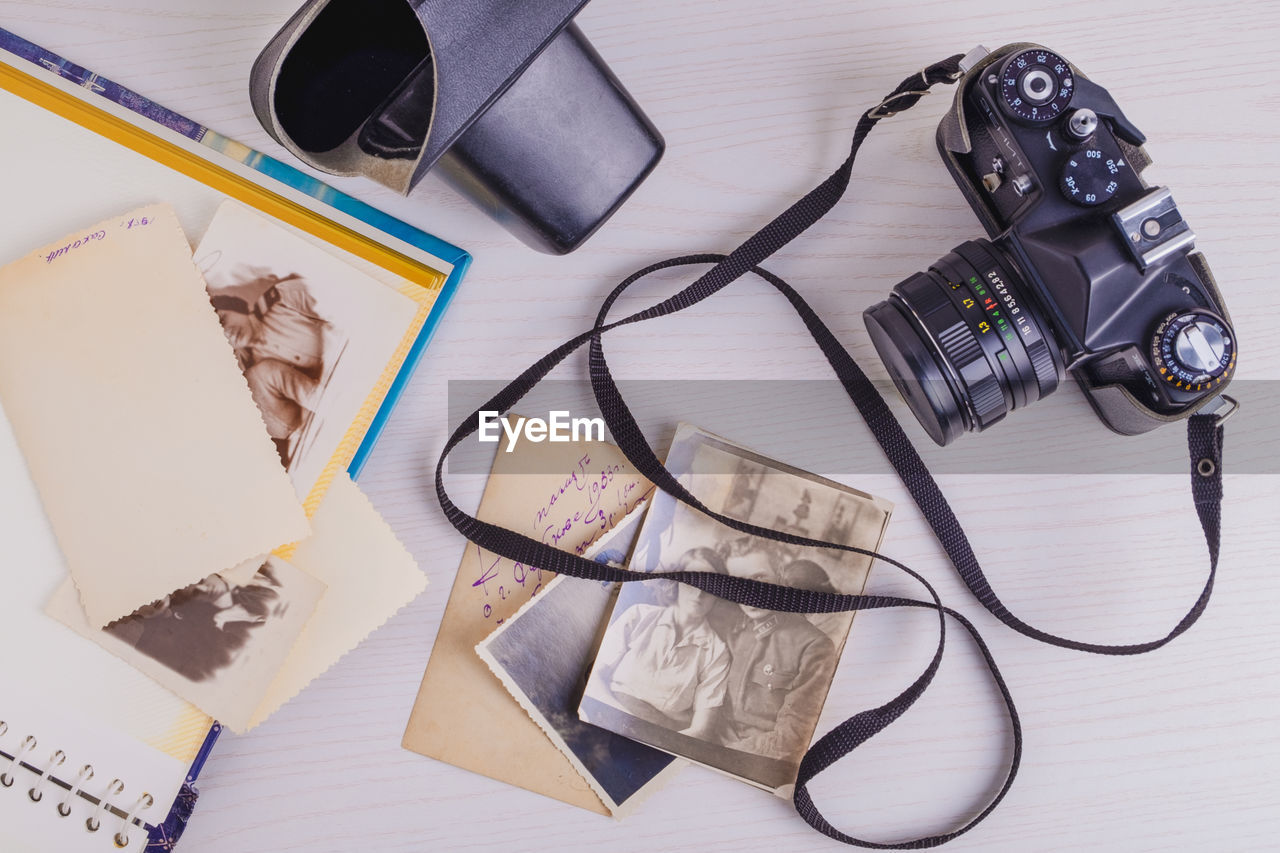 HIGH ANGLE VIEW OF DIGITAL CAMERA ON TABLE WITH PAPER