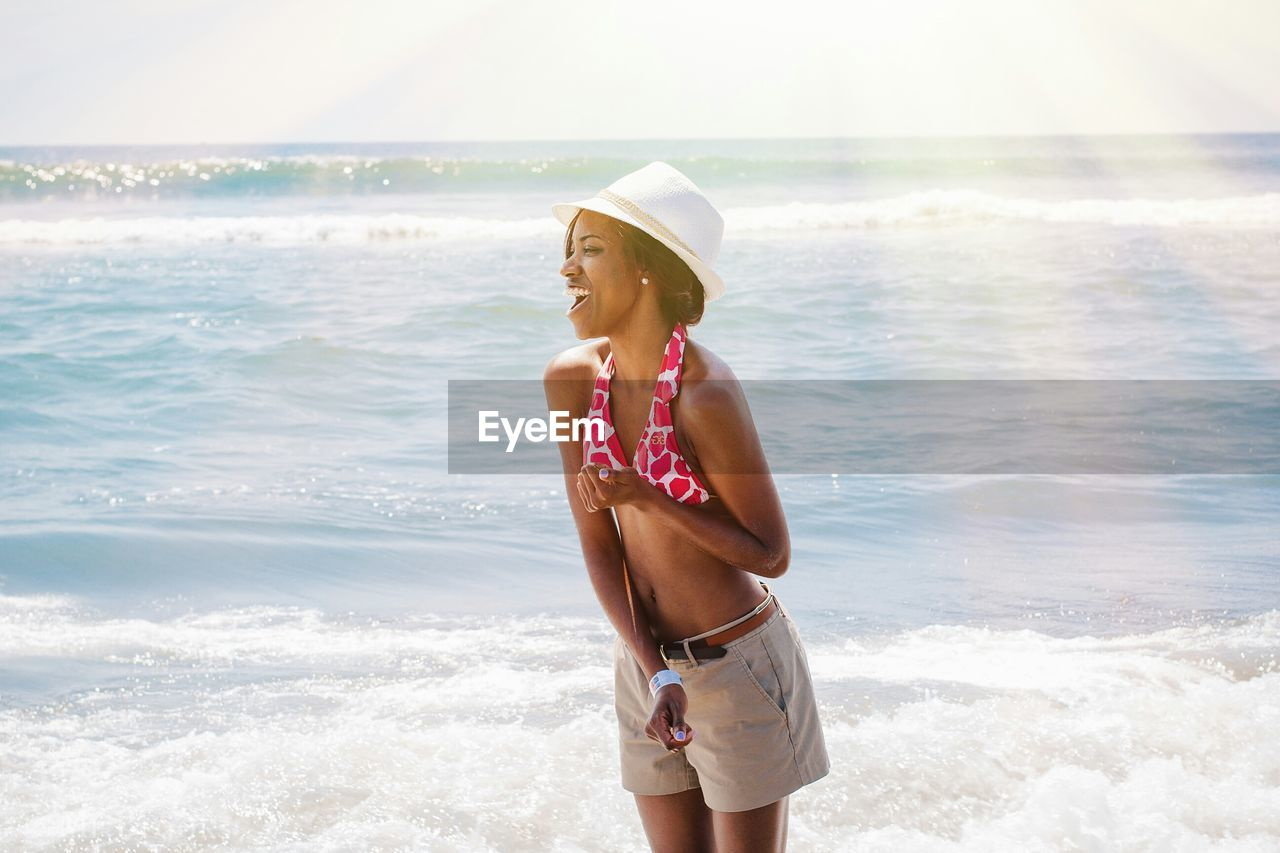Happy woman standing at beach on sunny day